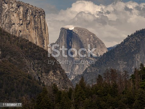 Half Dome view in Yosemite National Park California. A popular destination for viewing a magnificent granite dome. One of the most popular features at Yosemite Park. Hazy afternoon view.