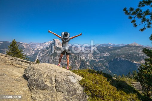 Travelling enthusiast woman happy for the Glacier Point aerial view in Yosemite National Park, California, US. Glacier Point panorama: Half Dome, Liberty Cap, Yosemite Valley, Vernal Fall, Nevada Fall