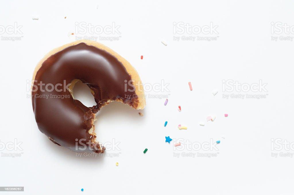 Half eaten chocolate doughnut with sprinkles stock photo