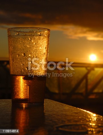 A part empty glass struck by the early morning sun.