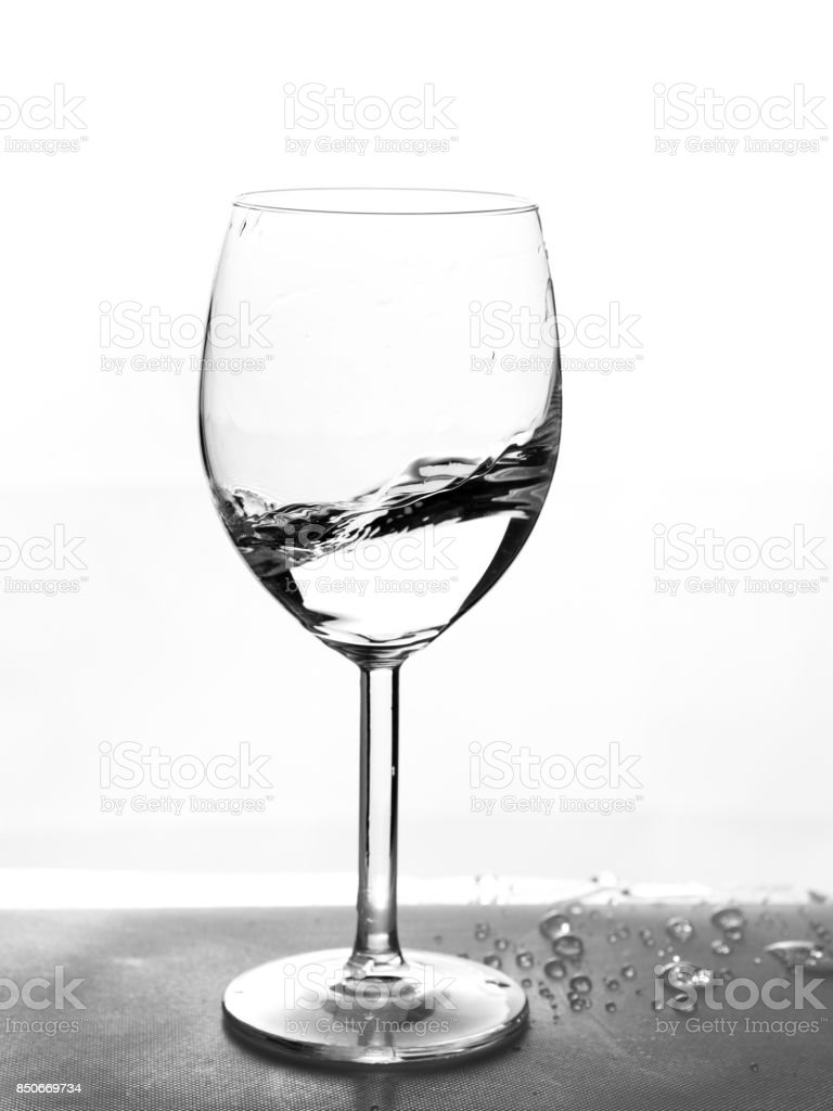 Half empty glass with water in motion stock photo