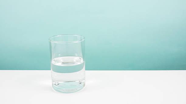 Half empty or half full glass of water stock photo