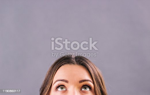 Closeup beautiful young woman looking up on blank copy space isolated on gray background. Attractive funny girl staring above her head. Half face of adorable woman thinking about solution. Empty space