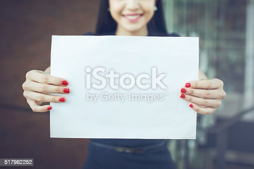 istock Half face of business woman holding an empty sign 517962252