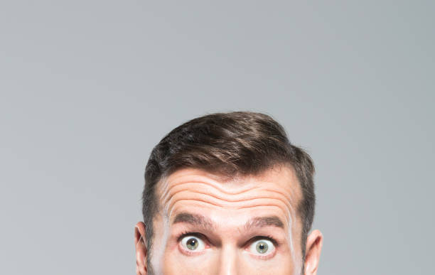 Half face of surprised man Cropped shot of mid adult man with surprised expression. Half face of mature man with eyes wide open. raised eyebrows stock pictures, royalty-free photos & images