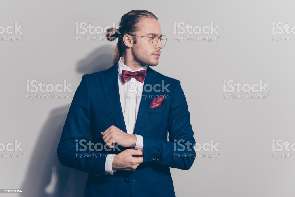 Half face portrait of stylish attractive bearded man in blue jacket with red bowtie correcting buttons on his sleeve of white shirt , turned face to the side with a serious expression, standing over  grey background stock photo