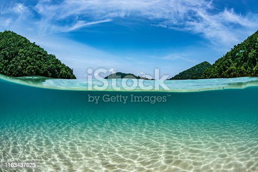 half frame of sea and sand underwater with blue sky