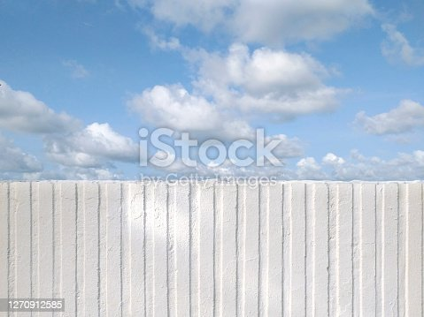 Half Front view of white vertical striped plaster under tropical blue sky. White rough cement wall with vertical grungy lines. Design Concrete wall vertical stripes pattern. French west indies.