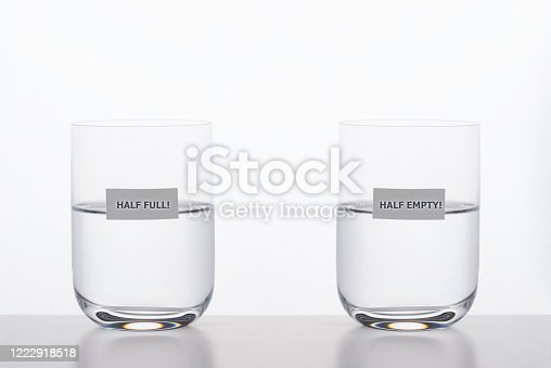 Two drinking glasses with water on white background. Half full is written on one glass and half empty on the other glass. Representing different  point of views about the same facts.