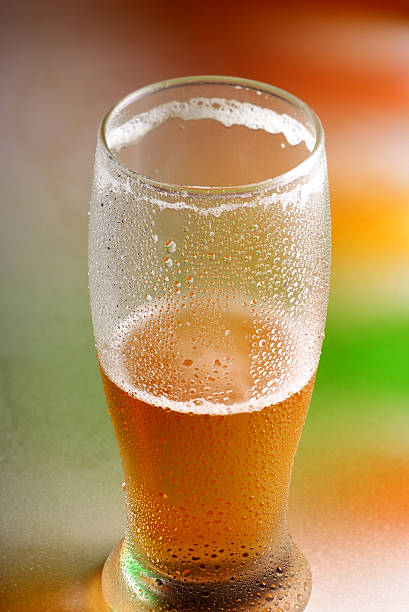 Half full beer glass over  multicolored background stock photo