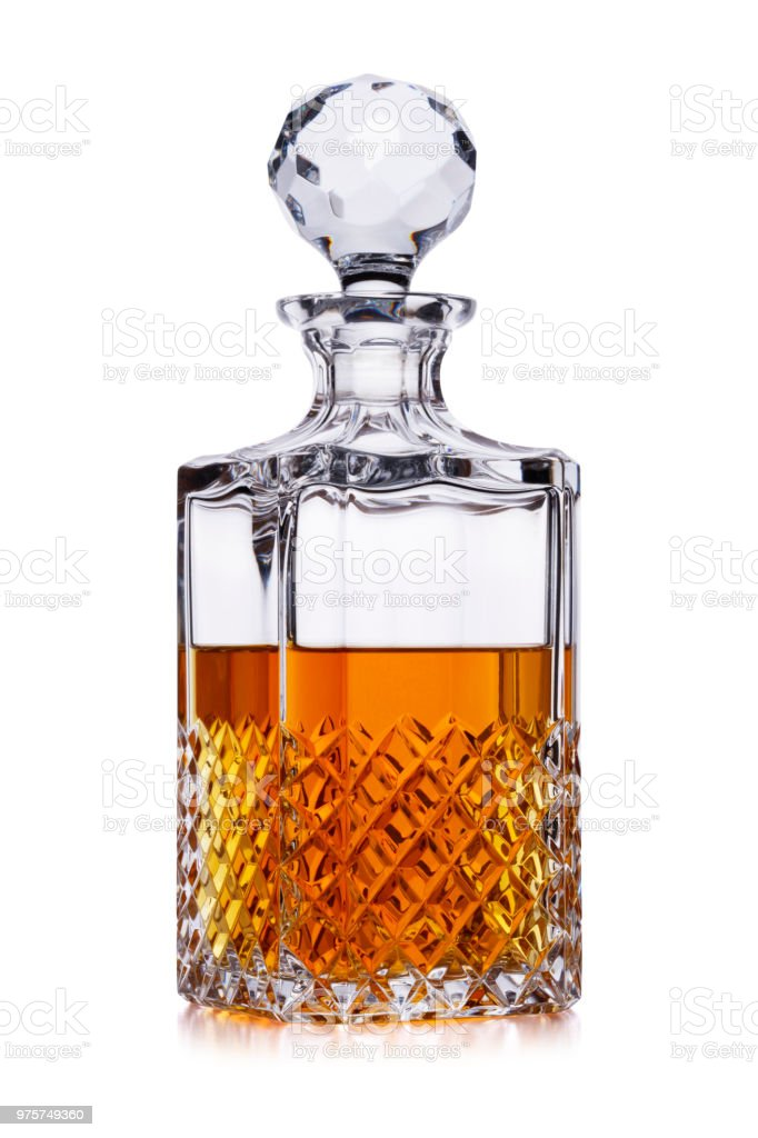 A half full crystal whisky decanter, with amber alcohol, shot on white, with a small reflection stock photo