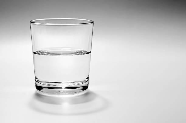 Half full, half empty glass of water stock photo