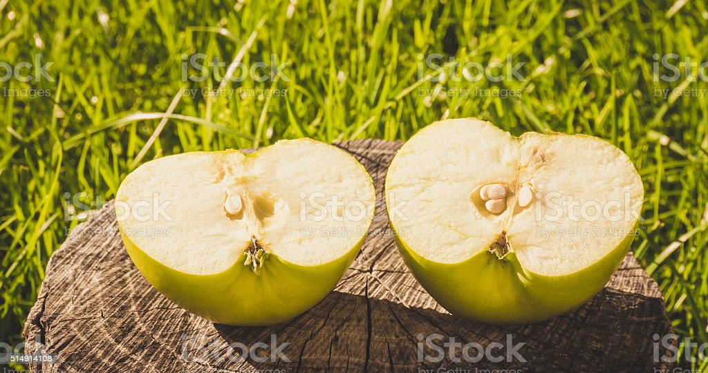 Half green Apple on the background of an old wood stock photo