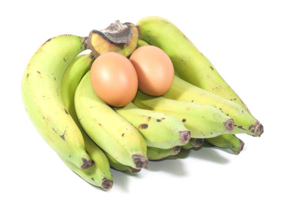 Half green half yellow bananas with some stains and two big eggs  taken on white screen, good for food content stock photo