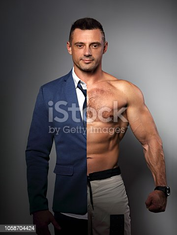 istock Half happy success business man in style blue suit and half of strong athlete with biceps on grey background. Concept photo of motivation in sport and health in one person 1058704424