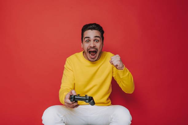 half length of screaming brown-haired guy holding joystick on red background - man joystick imagens e fotografias de stock