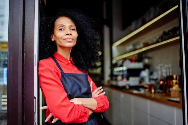 Half length portrait of confident african american young woman with crossed hands working barista while standing at entrance to bakery.Experienced dark skinned owner of cafe developing retail business stock photo