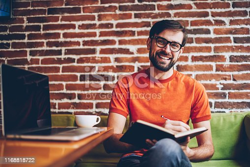 1174436608 istock photo Half length portrait of successful bearded young man in eyewear smiling at camera while writing down text information in notepad to plan working process sitting at modern netbook in coworking space 1168818722
