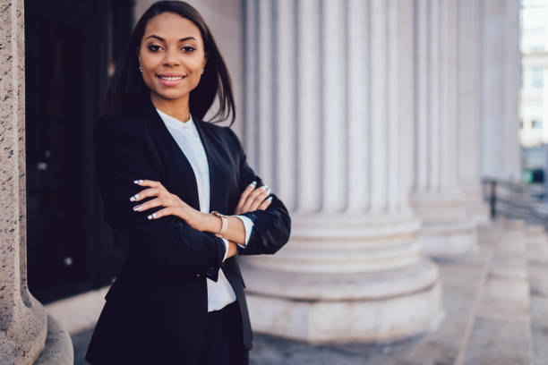 Half length portrait of successful happy businesswoman with dark skin crossed arms smiling at camera.Prosperous African American financial manager dressed in formal wear standing near copy space stock photo