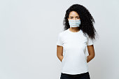 istock Half length shot of Afro American woman being on self isolation or quarantine, wears medical mask during coronavirus outbreak, listens news, tries not to spread virus, stays at home for long period 1215728674