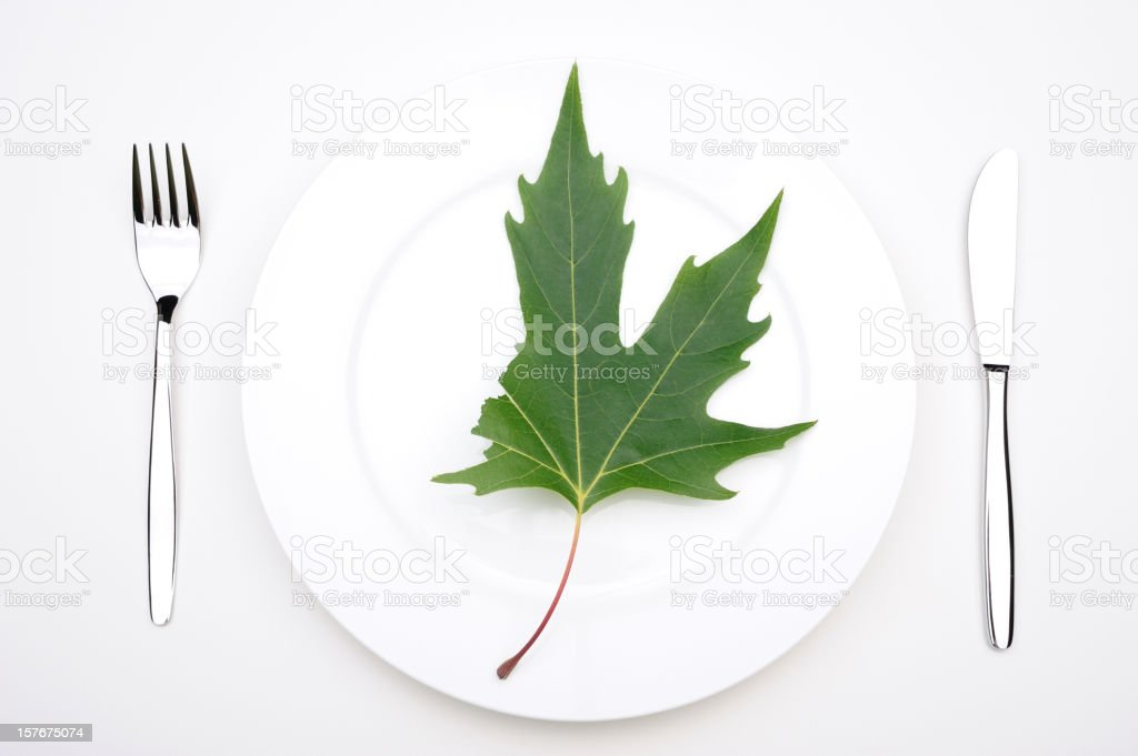 Half maple leaf on a plate royalty-free stock photo