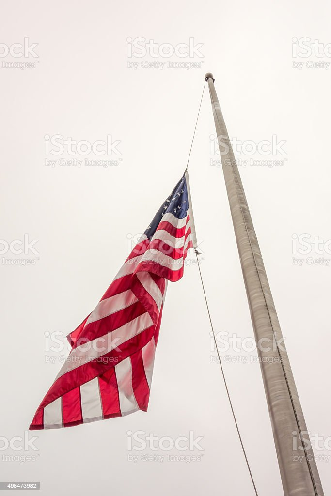 Half mast American flag concept stock photo