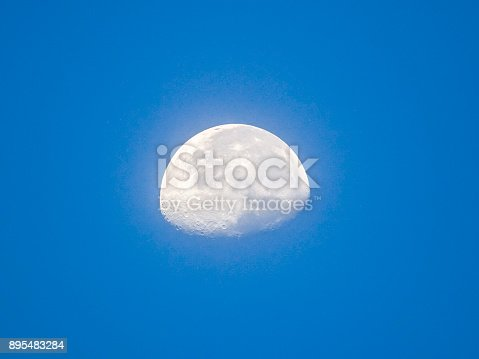 Half moon concept. Half moon daytime blue background. It is a black and white image that see details on the surface. Look again is awesome suitable for background. Moon orbit planet Earth.