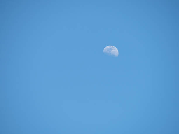 Half moon in a clear blue afternoon sky stock photo