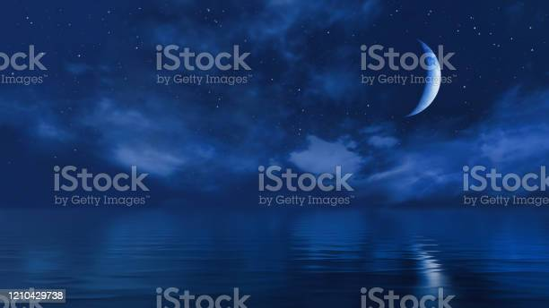 Photo of Half moon in starry night sky above ocean surface