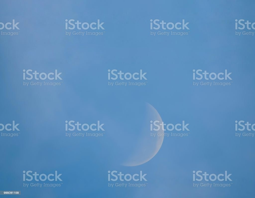 Photograph of the moon in its half shape in the morning sky.