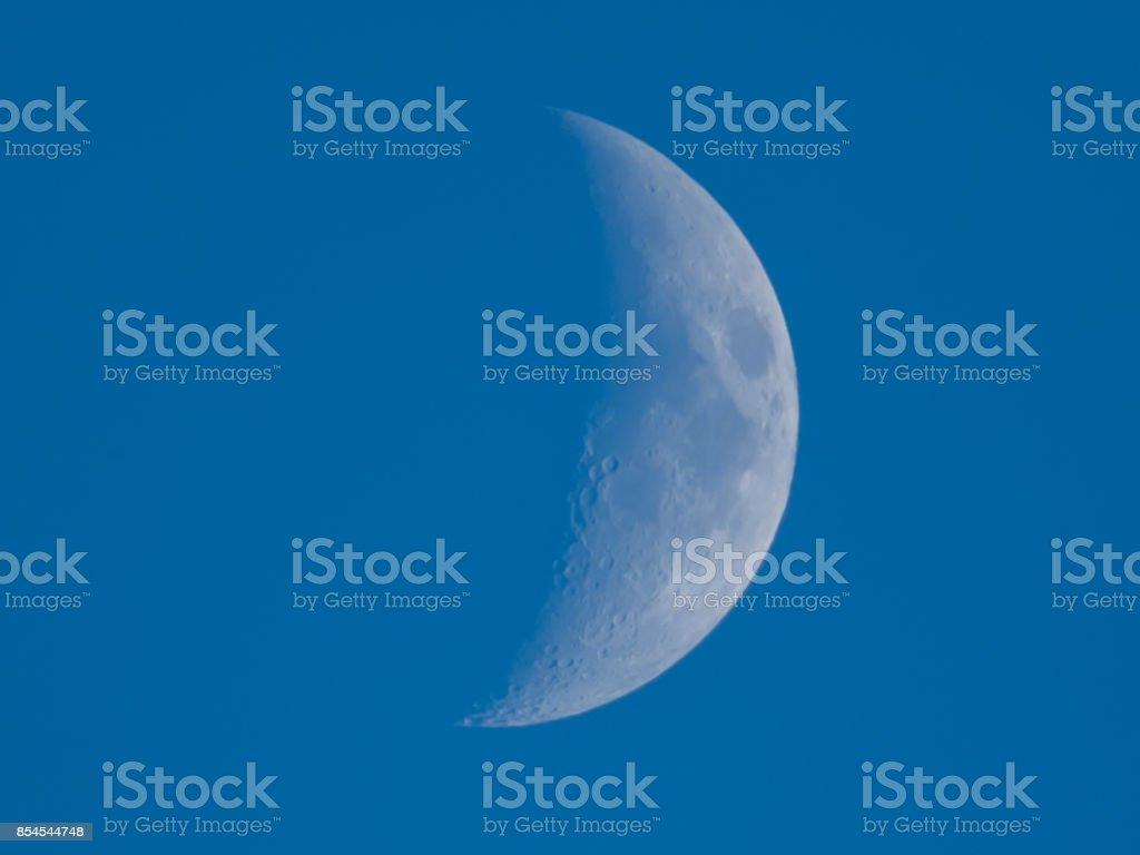 half moon on day on blue sky stock photo