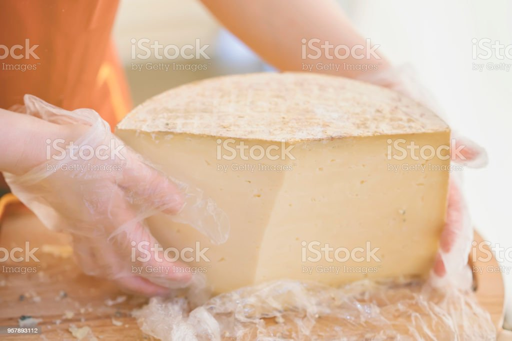 Half of a large head of cheese in the hands of the seller in gloves, wooden board. Selective focus. Gastronomic dairy produce, real scene, food market stock photo