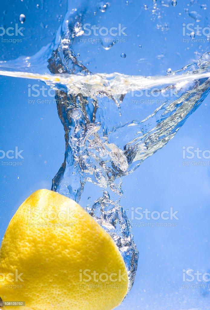 Half of a Lemon Splashing in Water royalty-free stock photo