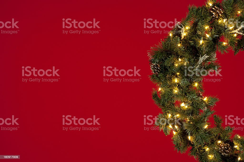 Half of a lighted Christmas wreath w/red background for text royalty-free stock photo