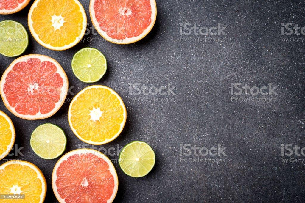 Half of citrus fruits on dark stone background stock photo
