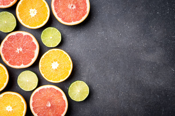 half of citrus fruits on dark stone background - agrume foto e immagini stock