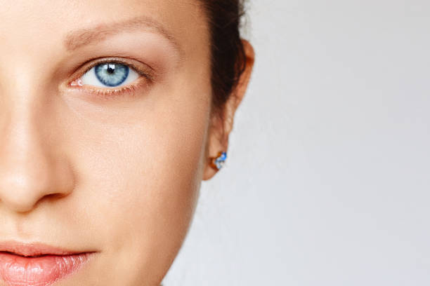 Half of female face with blue eyes without make-up over grey background stock photo