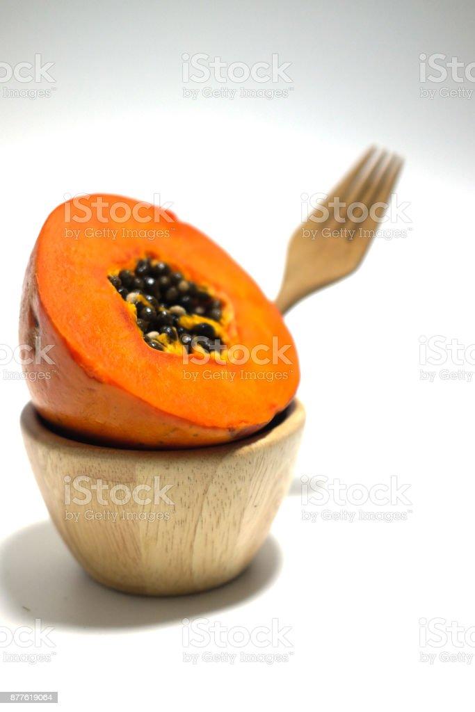 Half of freshly yellow orange papaya on wood bowl stock photo