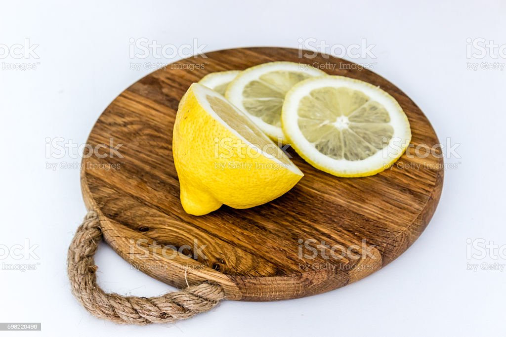 Half of lemon and slices on wooden cutting board foto royalty-free