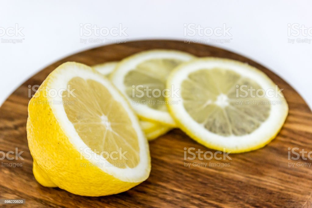 Half of lemon and three slices on wooden cutting board foto royalty-free