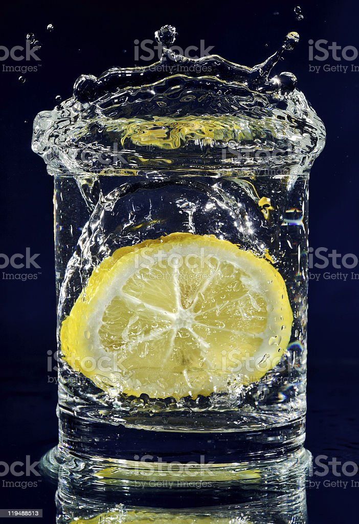 Half of lemon falling down in glass with water royalty-free stock photo