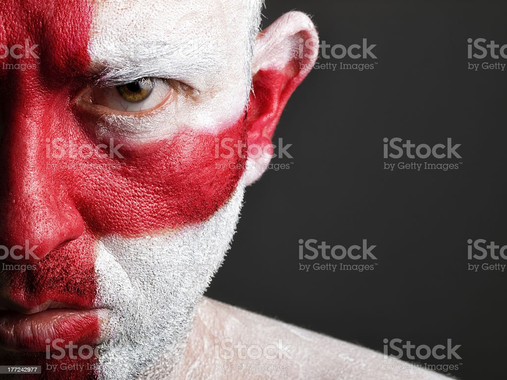 Half of man's face with white and red paint stock photo