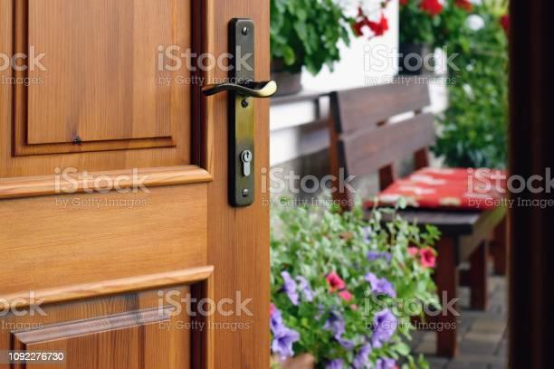 Photo of Half opened door into the beautiful summer terrace and  blooming garden