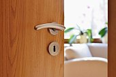 istock Half opened door into the cozy home interior 1092276718