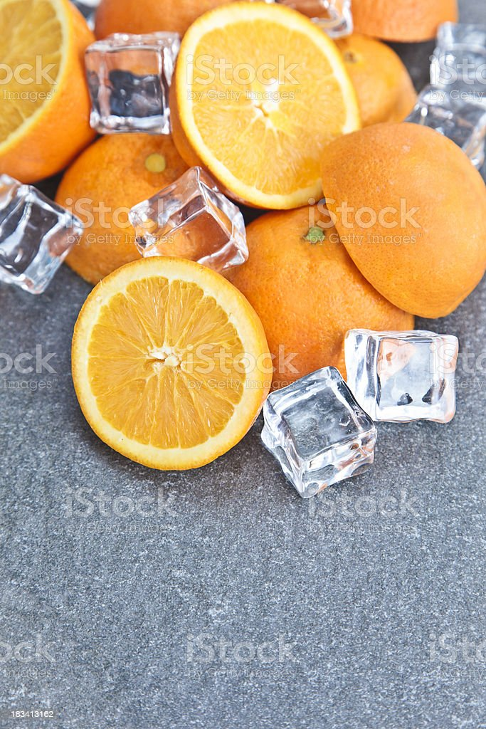 Half oranges granite table with icecubes royalty-free stock photo