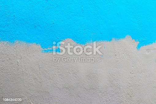 A wall half painted with blue colour.