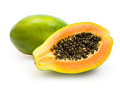 Half papaya showing orange flesh and dark seeds green skin