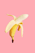 Half peeled banana on a pink background.