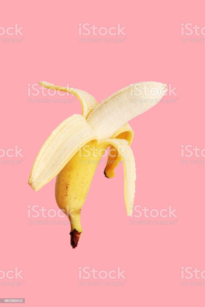 Half peeled banana on a pink background. stock photo