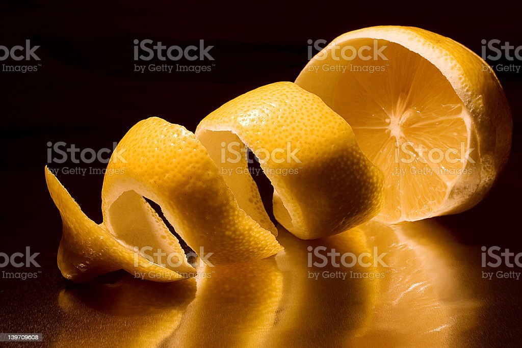 A half peeled lemon with the peel in a twist on a dark back royalty-free stock photo